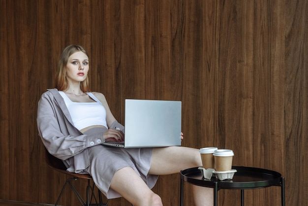 Young stylish woman sitting with a laptop and looking at the camera