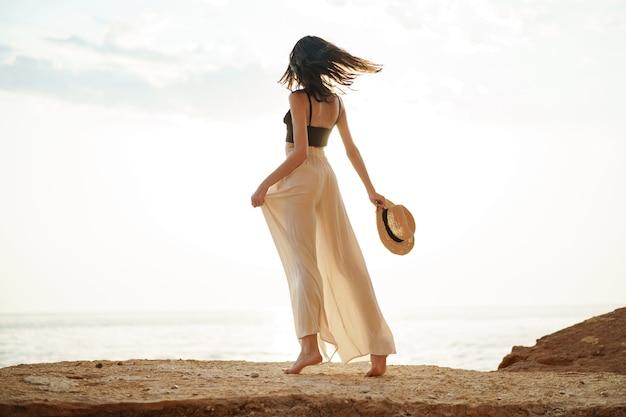 夕暮れ時の海の崖の上に立っている若いスタイリッシュな女性