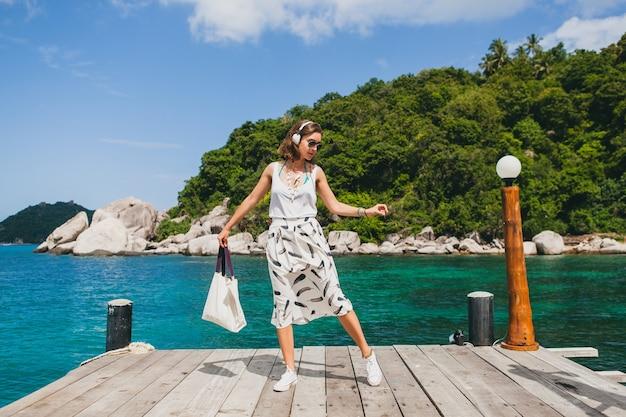 桟橋に立って、歩いて、ヘッドフォンで音楽を聴いて、夏のアパレル、白いスカート、ハンドバッグ、紺碧の水、風景の背景、熱帯のラグーン、休暇、アジア旅行
