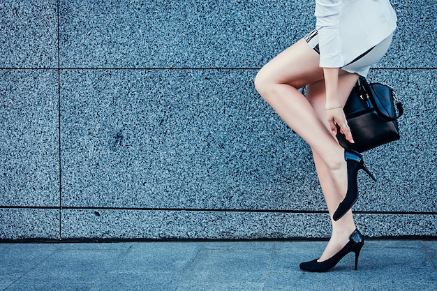 若いスタイリッシュな女性は、屋外の壁にかかとをチェックするために立ち止まった