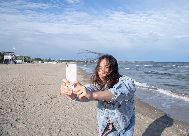 Young stylish woman takes a selfie photo by the sea on the beach.