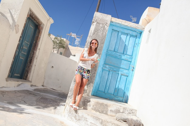Young stylish woman talking on phone and standing near blue door in the greek village of emporio