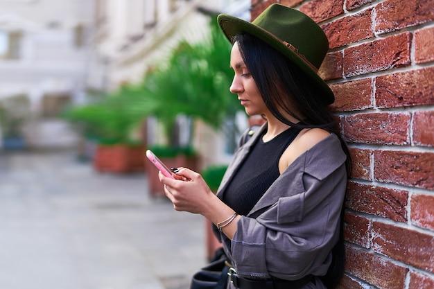 Молодая стильная женщина-путешественница с помощью смартфона и стоя у кирпичной стены