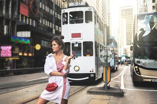香港の街の通りを歩いている若いスタイリッシュな女性