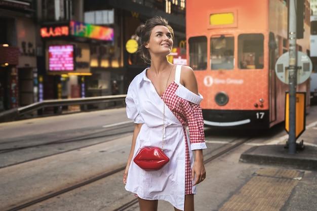 Молодая стильная женщина гуляет по улице города гонконг