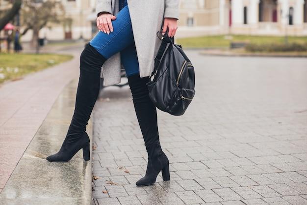秋の街、寒い季節にハイヒールの黒のブーツ、革のバックパック、アクセサリー、グレーのコートを着て、ベンチ、ファッショントレンド、足のクローズアップの詳細に座っている若いスタイリッシュな女性