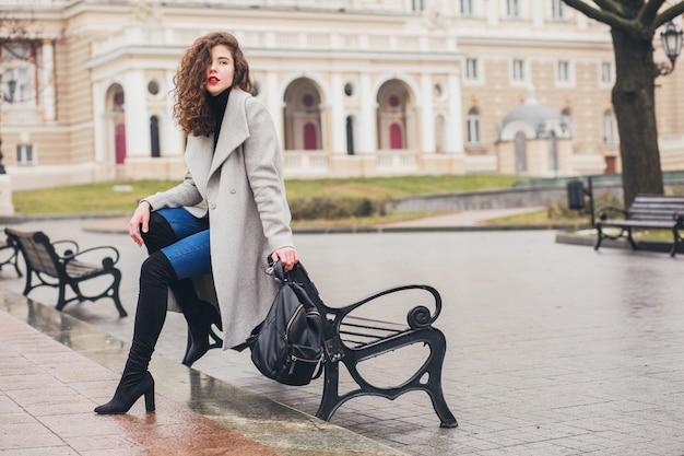 秋の街、寒い季節に歩くハイヒールの黒のブーツ、革のバックパック、アクセサリー、グレーのコート、ベンチ、ファッショントレンドに座っている若いスタイリッシュな女性