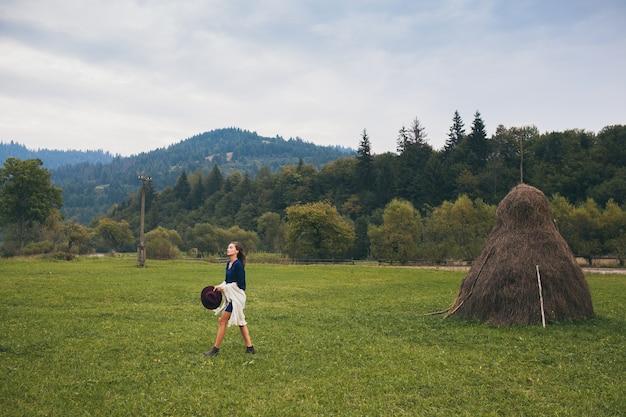Молодая стильная женщина гуляет в сельской местности в осеннем наряде зеленых гор и полей