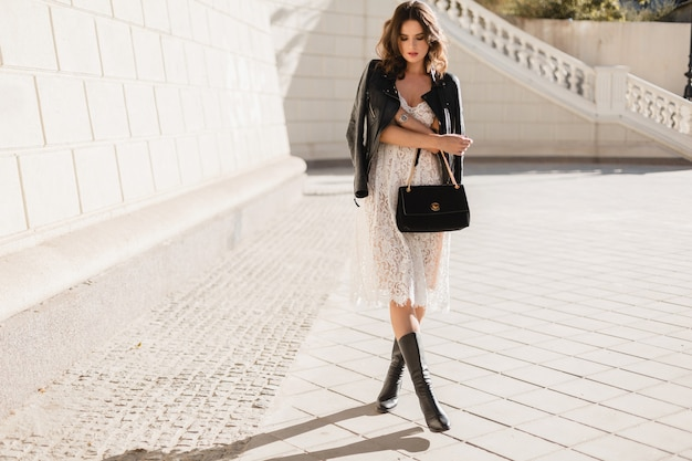 Молодая стильная женщина гуляет по улице в модной одежде, держит сумочку, в черной кожаной куртке и белом кружевном платье, в весенне-осеннем стиле, позирует, в высоких кожаных сапогах