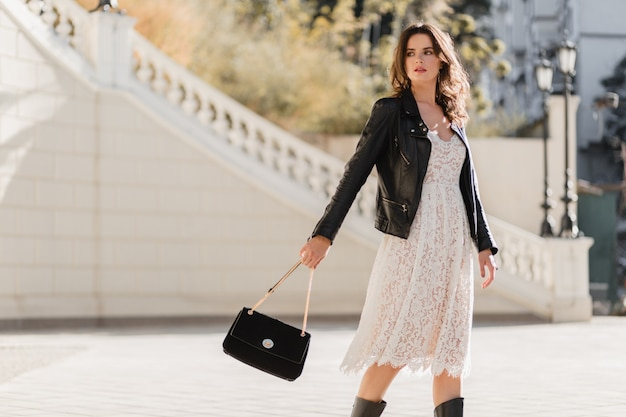ファッショナブルな服装で通りを歩いている若いスタイリッシュな女性、財布を持って、黒い革のジャケットと白いレースのドレスを着て、春秋のスタイル、ポーズ、ハイレザーのブーツ