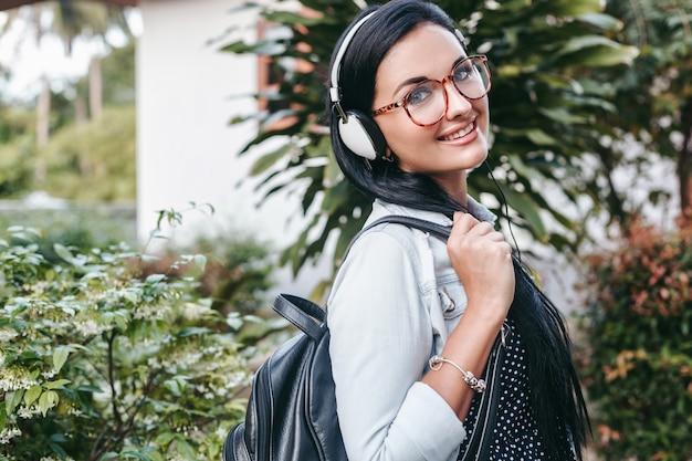 歩く、ヘッドフォンで音楽を聴く、笑顔、幸せ、バックパックを持って、夏休みのスタイリッシュな若い女性