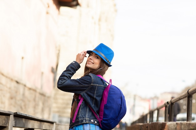 Young stylish woman walking on the old town street, travel with backpack and blue hat. ukraine, lviv