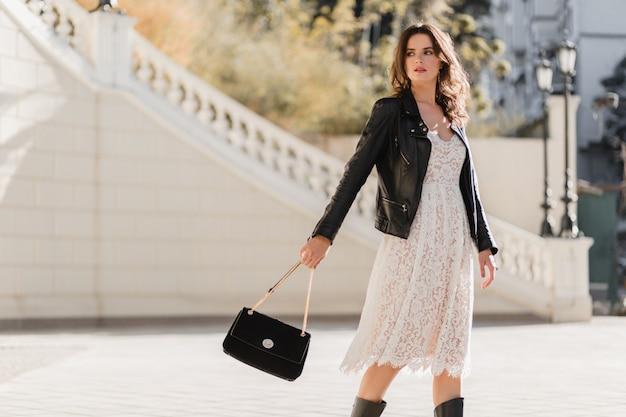 Giovane donna alla moda che cammina in strada in abito alla moda, tenendo la borsa, indossa una giacca di pelle nera e abito di pizzo bianco, primavera autunno stile, posa, stivali di pelle alti