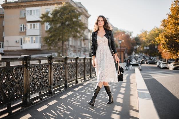 Giovane donna alla moda che cammina in strada in abito alla moda, tenendo la borsa, indossa una giacca di pelle nera e abito di pizzo bianco, stile primavera autunno