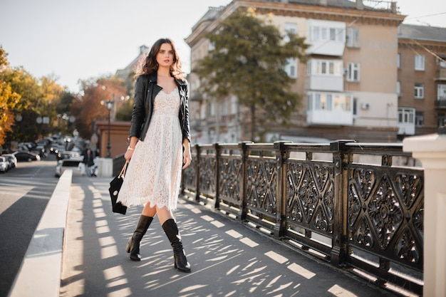 Young stylish woman walking in street in fashionable outfit, holding purse, wearing black leather jacket and white lace dress, spring autumn style