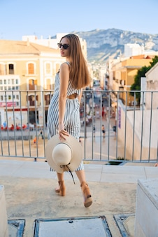 Young stylish woman walking on the street holding straw hat in hands on sunny day.