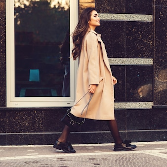 Young stylish woman walking in street. woman wearing trendy coat, fashion shoes and holding black handbag. fashion female blooger going shopping. fashion, lifestyle, shopping