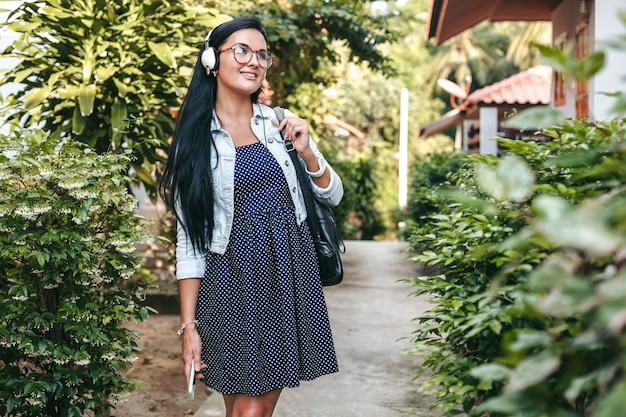 Giovane donna alla moda che cammina con lo smartphone, ascoltando musica in cuffia, vacanze estive