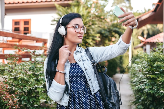 Young stylish woman walking with smartphone, listening to music on headphones, taking photo, vintage denim style, summer vacation