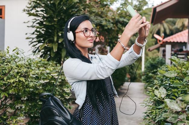 Молодая стильная женщина гуляет со смартфоном, слушает музыку в наушниках, фотографирует, винтажный джинсовый стиль, летние каникулы