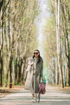 Young stylish woman walks with white dog