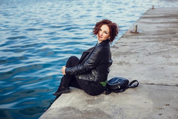 秋の季節に街を歩いている黒いコート、ズボン、ハンドバッグを身に着けている若いスタイリッシュな女性。冬のファッション、エレガントな外観、。プラスサイズモデル。