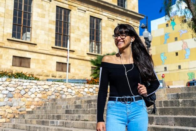 離れて音楽を聴いて立って屋外で自由な時間を過ごすイヤホンを身に着けている若いスタイリッシュな女性