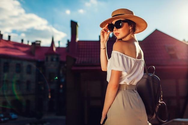屋外で帽子とサングラスを身に着けている若いスタイリッシュな女性。レトロな服を着てリヴィウを歩くバックパックと電話を持つスタイリッシュな女の子
