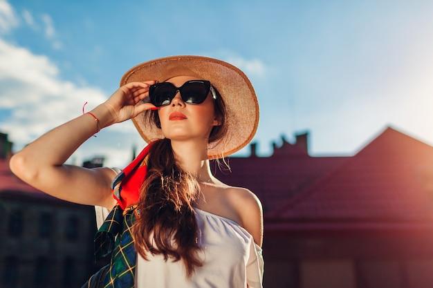 屋外で帽子とサングラスを身に着けている若いスタイリッシュな女性。レトロな服を着てリヴィウを歩くバックパックを持つスタイリッシュな女の子