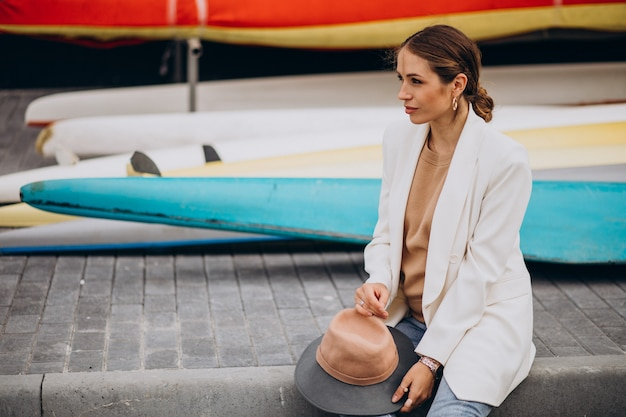 Young stylish woman in white jacket travelling