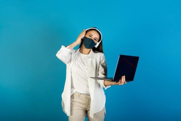 Молодая стильная женщина с маской и наушниками держит портативный компьютер и слушает музыку.