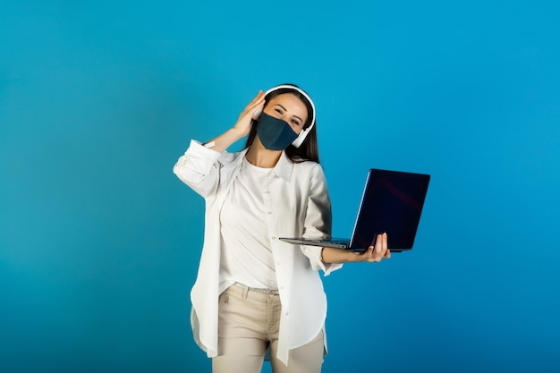 Young stylish woman with face mask and headphones is holding laptop computer and listen the music.