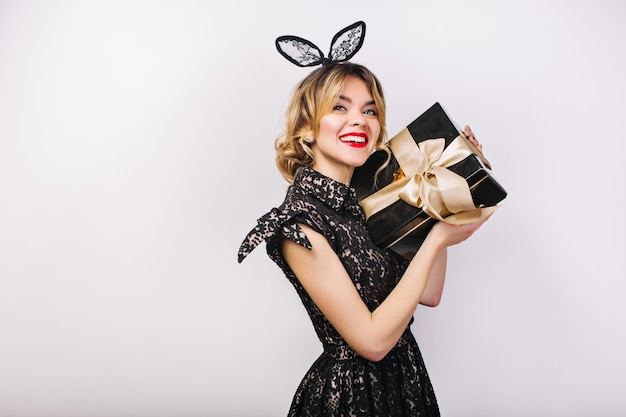 Young stylish woman with gift box, celebrating, wearing black dress and black crown, happy birthday party, having fun.