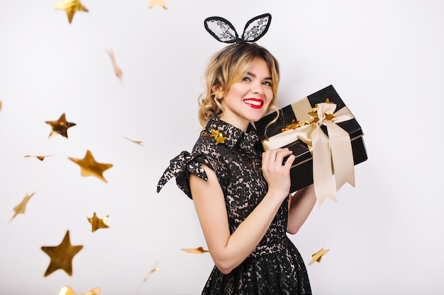 Giovane donna alla moda con confezione regalo, festeggia, indossa un abito nero e corona nera, festa di buon compleanno, coriandoli d'oro scintillanti, divertirsi.