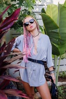 분홍색 보라색 머리띠와 검은 색 허리 가방 야외 포즈와 젊은 세련된 여자