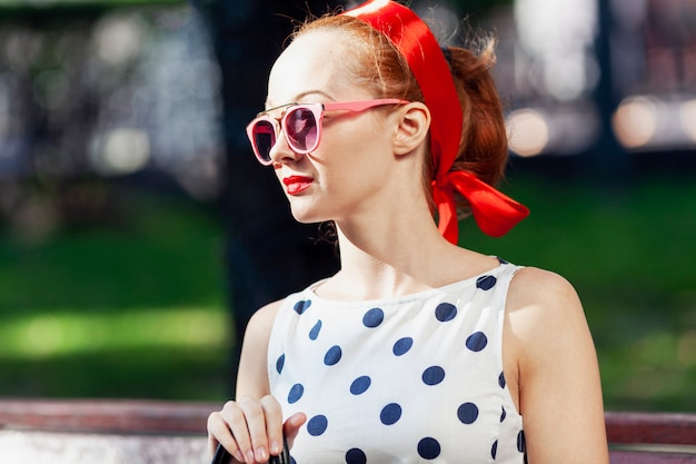 Young stylish woman with red hair and sunglasses in the park on a sunny day.
