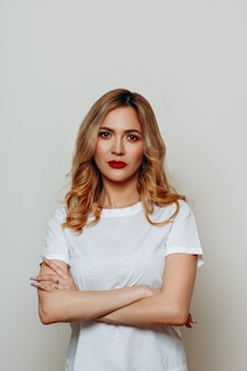 赤い唇を持つ若いスタイリッシュな女性は白に真剣に見えます。