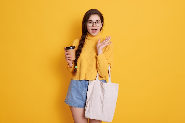 Young stylish young woman wearing shirt and short, lady holding bag and take away coffee