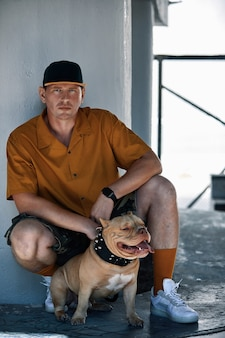 도시 거리에 미국 깡패 개와 함께 세련 된 옷을 입고 젊은 남자.