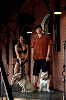 Young stylishly dressed man and woman with an athletic figure with two american bully dogs under the bridge on city streets.