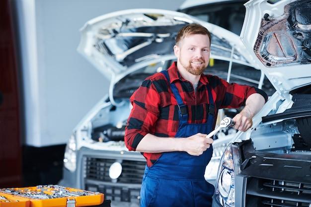 修理中の自動車のそばに立っているフランネルとオーバーオールの若い成功したプロの自動車修理工