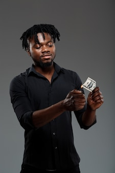 Young successful african businessman burning money on dark