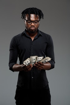 Young successful african businessman holding money on dark