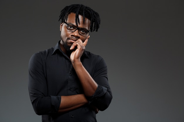 Молодой успешный африканский бизнесмен в очках позирует на темном