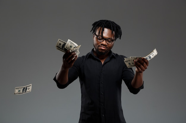 Young successful african businessman throwing money on dark