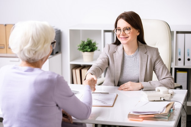 Young successful agent looking at retired female with smile while shaking her hand over desk after signing documents
