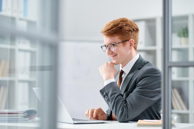 Молодой успешный аналитик или финансист, работающий с онлайн-данными на дисплее ноутбука в офисе