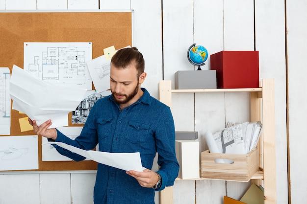 Молодой успешный архитектор, глядя на рисунки, стоя в офисе