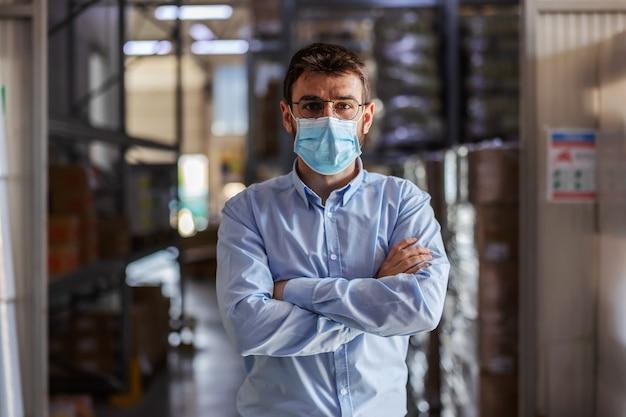 腕を組んで倉庫に立ってカメラを見ているサージカルマスクを持つ若い成功した魅力的なビジネスマン。コロナ発生の概念。
