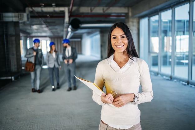 건설 과정에서 건물 내부에 서서 서류를 손에 들고 젊은 성공적인 매력적인 백인 여성 건축가.